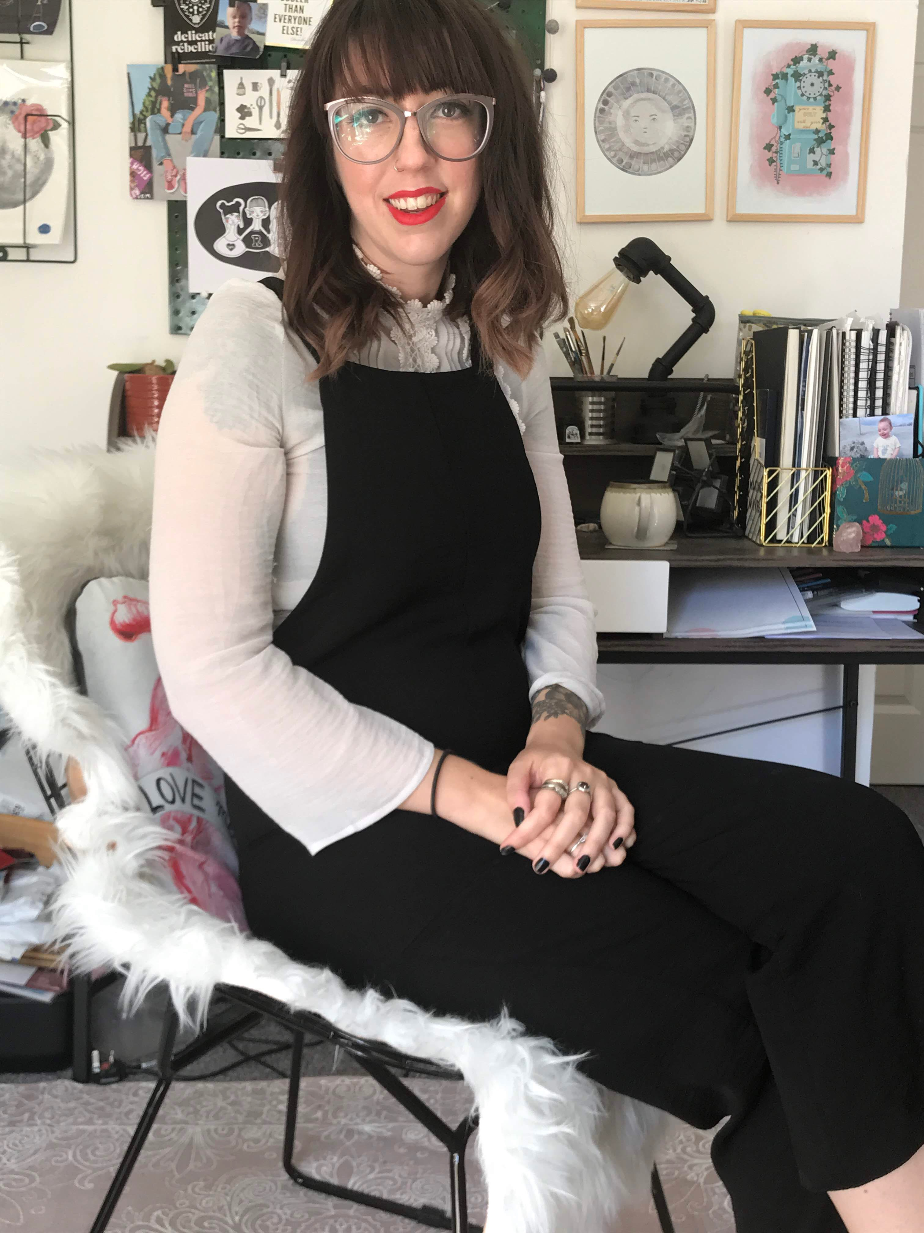 Hannah Raymond of ink and tot sitting in chair in front of desk with art work on the wall behind